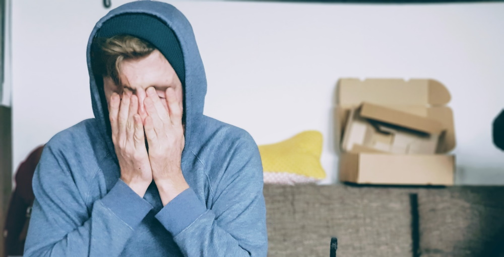 A man in a hooded sweatshirt feeling anxious worried and financially insecure